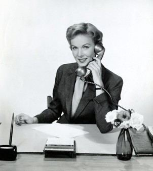 Woman Talks on Office Phone While Seated at Desk